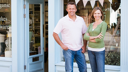 smiling man and woman in front of store